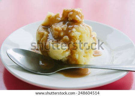 Mashed potato with gravy poured over.  - stock photo