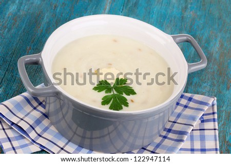 Mashed potatoes in saucepan on blue wooden table