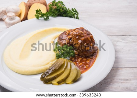 Mashed potatoes with meat cutlet on white plate - stock photo
