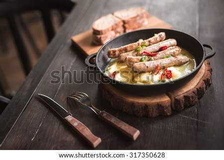 mashed potatoes with sausages grilled in a pan on wooded table - stock photo