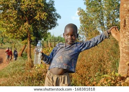 MASINDI DISTRICT, UGANDA - DECEMBER 9: Unidentified small beggar on the road to Murchison Falls on December 9, 2007 near Masindi, Uganda. Begging for tourists is common for children in rural Uganda. - stock photo