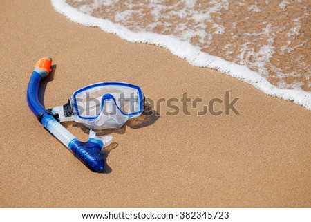 Mask and snorkel in the surf on the sandy beach; selective focus