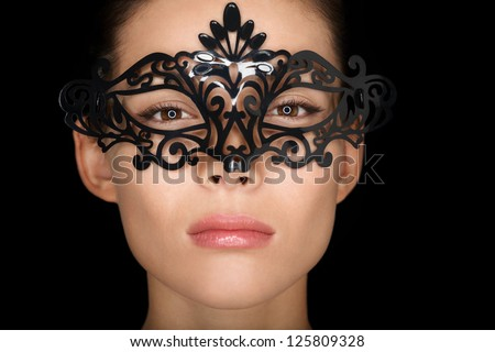 Mask. Beauty woman wearing carnival mask isolated on black background. Close up portrait of young mixed race Asian Caucasian girl hiding behind mask. - stock photo