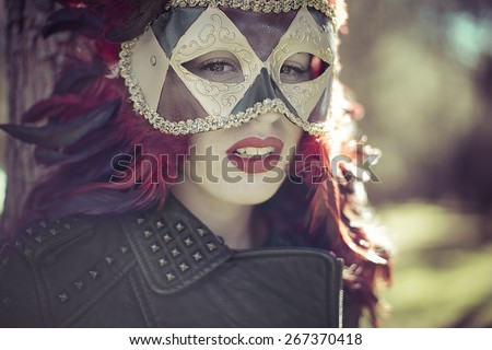 Mask brunette woman with flowing hair and jacket with golden wings - stock photo