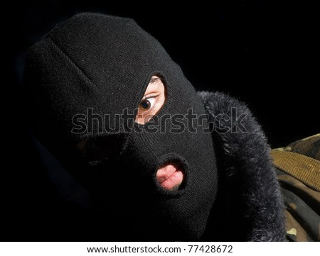 mask commando.portrait of man in a face-guard on a black background - stock photo