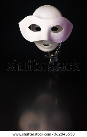 Mask in the mask, iron alligator clip stand with two white masks on a black background - stock photo