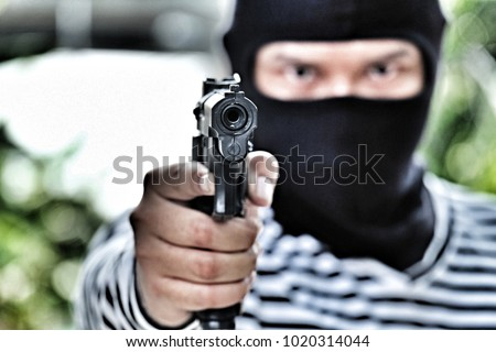 Mask thief in balaclava with holding gun ,Outlaw bad man hold a gun pointing the target , robber in black hood holding gun and pointing to photographer