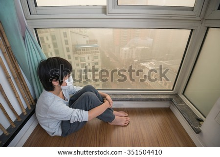 Mask-wearing boy looking outside the window on extremely polluted day - stock photo