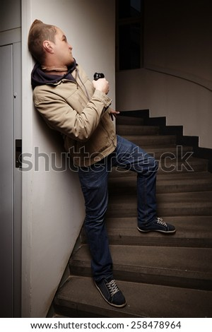 Masked armed man with pistol waiting for his victim - stock photo