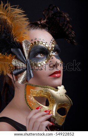 Masked beautiful woman  holding a glittered mask - stock photo