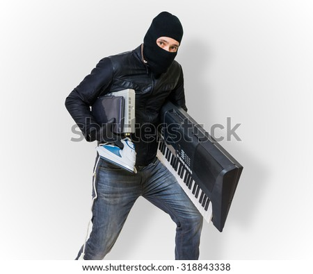 Masked burglar or thief with balaclava is stealing electronic appliances. - stock photo