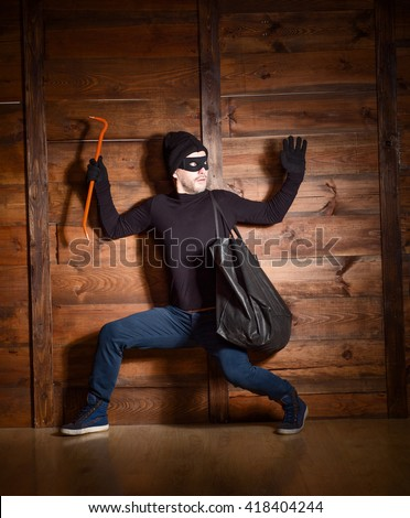 Masked burglar wearing black clothes was caught by police near house in which he wanted to break in.  - stock photo