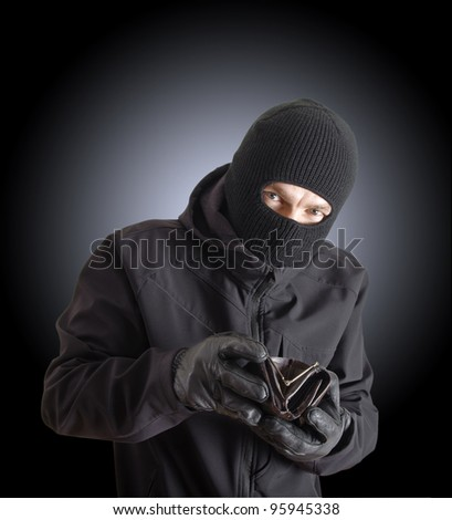 Masked criminal holding a stolen leather purse
