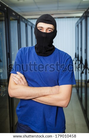 Masked cyber hacker wearing a balaclava stands in data center on the background.