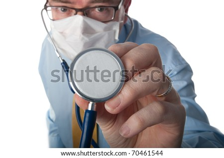 Masked doctor looks at camera and hold stethoscope close to viewer. Focus on equipment - stock photo