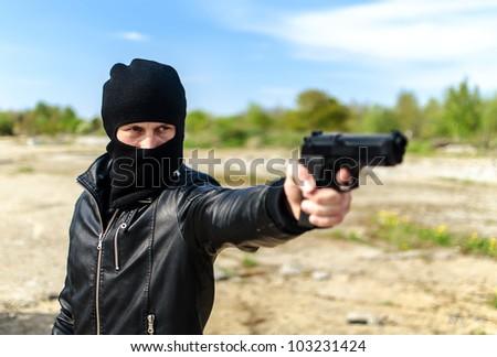 Masked gunman taking aim with a gun - stock photo