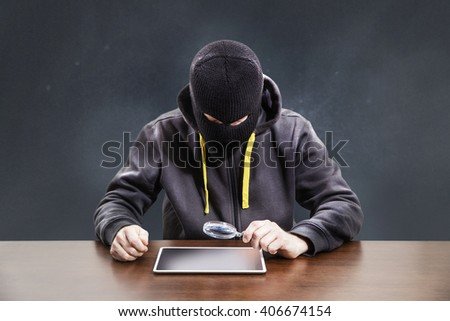 Masked hacker stealing passwords form mobile device tablet