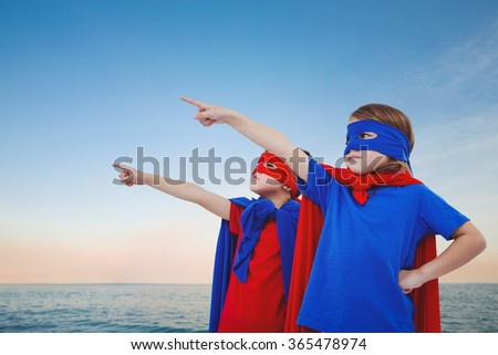 Masked kids pretending to be superheroes against beautiful sunset on a sunny day - stock photo