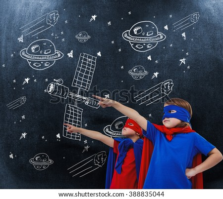 Masked kids pretending to be superheroes against black background - stock photo