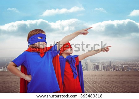 Masked kids pretending to be superheroes against city on the horizon - stock photo