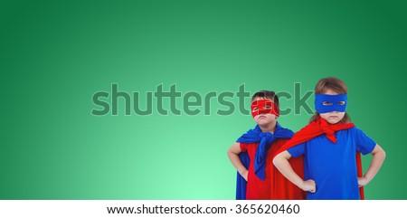 Masked kids pretending to be superheroes against green vignette - stock photo