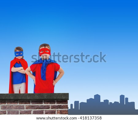 Masked kids pretending to be superheroes against red brick wall - stock photo