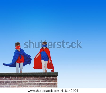 Masked kids running pretending to be superheroes against red brick wall - stock photo