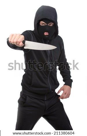 Masked man aims with knife. on gray background