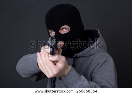 masked man criminal aiming with gun over grey background - stock photo