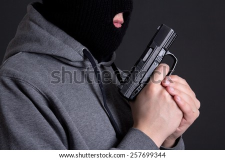 masked man criminal holding gun over grey background - stock photo