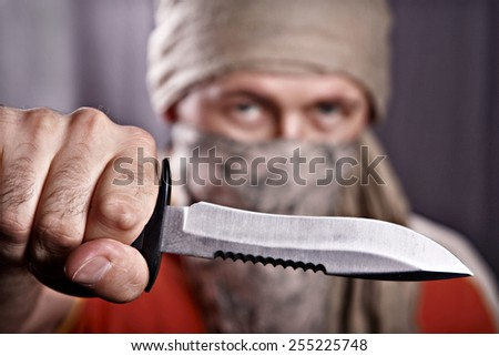 masked man holding a knife on a black background, focus forward - stock photo
