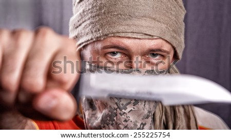 masked man holding a knife on a black background, focus on eyes - stock photo
