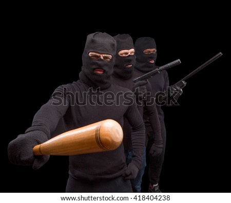 Masked men preparing to attack with bats, rifles and guns over black background. Men are going to sreal something or someone. Isolated on black. - stock photo