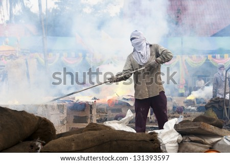 Masked people preparing the ground in a ceremony to make a Buddhist temple in rural Thailand