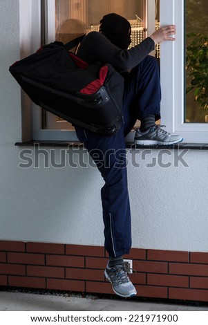 Masked robber entering the house with bag - stock photo