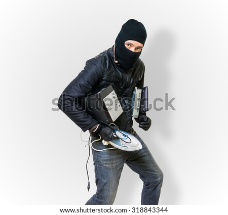 Masked robber or criminal with balaclava is stealing electronic appliances. - stock photo