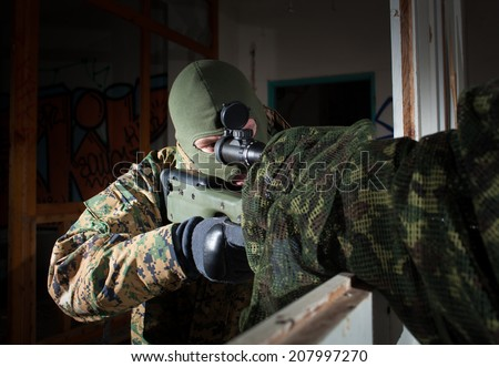 Masked sniper is aiming at the target during the mission (color toned image) - stock photo