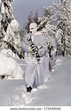 masked soldiers with weapons in the snow - stock photo