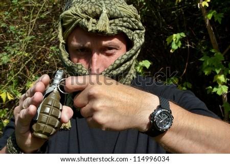 masked terrorist threatens grenade explosion - stock photo