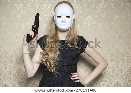 masked woman with a gun in hand - stock photo