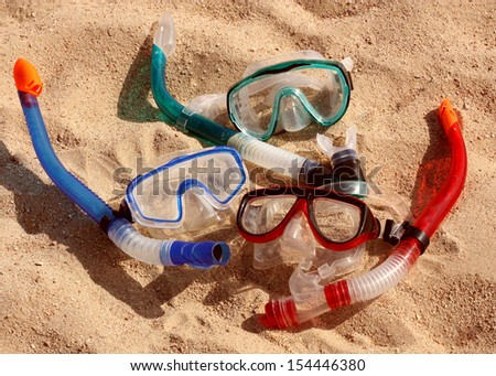 Masks and tubes for scuba diving lie on sand - stock photo