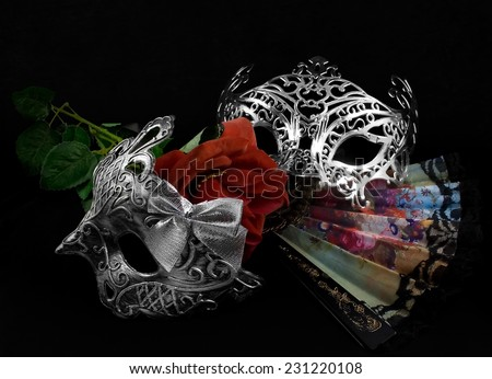 Masks with rose.Silver carnival masks laying with folding fan and red rose on black fabric background. - stock photo
