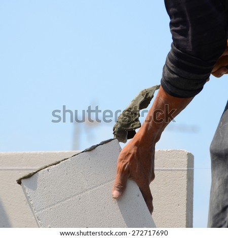 Mason brick walls were formed by mixing cement trowel to scoop sand and water until a homogeneous poured onto bricks to help the adhesion and strength. - stock photo