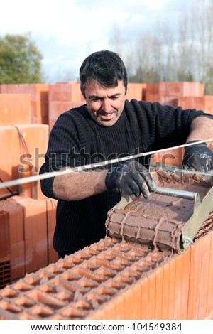 Mason carefully pouring cement on wall - stock photo