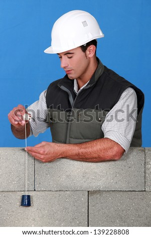 Mason checking quality of wall - stock photo