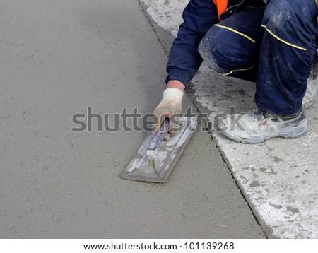 Mason concludes edge of the concrete surface - stock photo