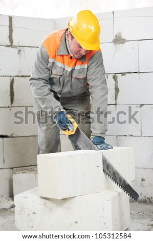 mason construction worker bricklayer sawing off a calcium silicate lime sand brick - stock photo