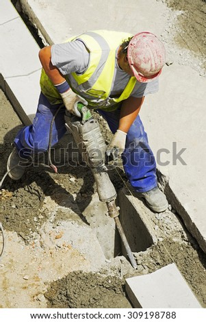 mason construction worker with pneumatic hammer drill equipment to repair  water and sewer pipes - stock photo