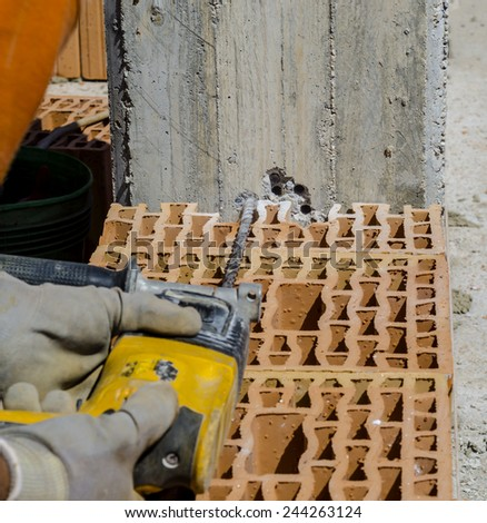 Mason drills a hole with a power drill on a column in of reinforced concrete. Selective focus on drill - stock photo
