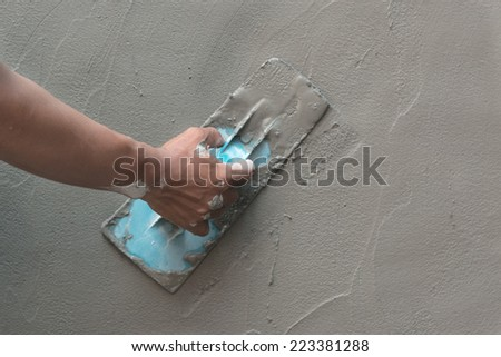 mason hand finishes a newly poured concrete floor  - stock photo